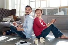 Middle-aged couple sitting on floor near window Stock Image
