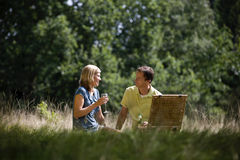 A middle aged couple sitting on the grass, having a drink Stock Photo