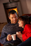 Middle Aged Couple Sitting With Hot Dri. Middle Aged Couple Sitting On Sofa By Cosy Log Fire With Hot Drink Royalty Free Stock Photo