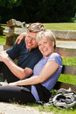 Middle aged couple sitting outside leaning against a fence. Stock Photography
