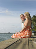 Middle Aged Couple Sitting On Pier Royalty Free Stock Photos