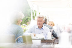 Middle-aged couple sitting at sidewalk cafe on sunny day Stock Images