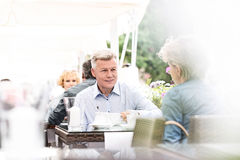 Middle-aged couple sitting at sidewalk cafe on sunny day Royalty Free Stock Image