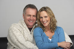 Middle Aged Couple Sitting On Sofa Stock Photo