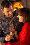 Middle Aged Couple Sitting Sofa By Cosy Log Fire. With Glass Of Champagne smiling at each other Royalty Free Stock Photography