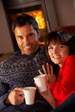 Middle Aged Couple Sitting On Sofa With Hot Dri. Middle Aged Couple Sitting On Sofa By Cosy Log Fire With Hot Drink Stock Images