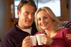 Middle Aged Couple Sitting On Sofa With Hot Drinks. In Chalet On Ski Holiday Smiling At Camera Royalty Free Stock Images
