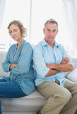 Middle aged couple sitting on the sofa not speaking after a disp. Ute with men looking at camera at home in the living room Royalty Free Stock Image
