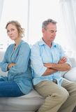 Middle aged couple sitting on the sofa not speaking after a figh. T with women looking at camera at home in the living room Stock Images