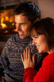 Middle Aged Couple Sitting Sofa Watching TV. By Cosy Log Fire Stock Images