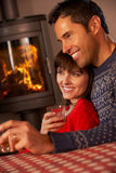 Middle Aged Couple Sitting On Sofa Watching TV. By Cosy Log Fire Royalty Free Stock Images
