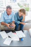 Middle aged couple sitting on their couch paying their bills Stock Image
