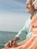 Middle Aged Couple Sitting By Water Stock Photo