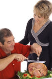 Middle aged couple slicing ham Royalty Free Stock Image