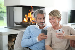 Middle-aged couple with smartphones by fireplace Royalty Free Stock Photo