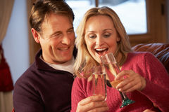Middle Aged Couple On Sofa With Champagne Stock Photos