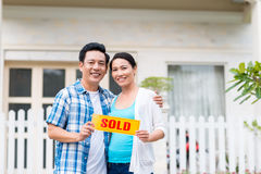 Middle-aged couple with sold sign Royalty Free Stock Photo