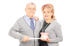 Middle aged couple standing close together holding dentures and Royalty Free Stock Image