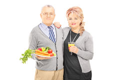 Middle aged couple standing close together holding a healthy foo Stock Images