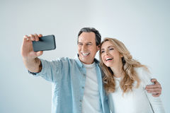 Middle aged couple standing embracing and taking selfie with smartphone stock photo