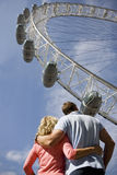 A middle-aged couple standing near London Eye, arm in arm royalty free stock photo