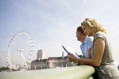 A middle-aged couple standing near the London Eye, looking at a guidebook Stock Photos