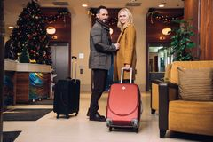 Middle aged couple standing with suitcases and smiling at camera in hotel hallway. At christmas royalty free stock image