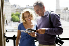 A middle-aged couple standing by Trafalgar Square, looking at a guidebook stock photography