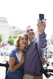 A middle-aged couple standing by Trafalgar Square, taking a photograph of themselves Stock Image