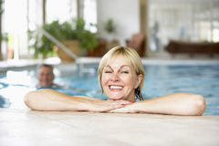Middle Aged Couple In Swimming Pool. Women smiling at camera stock images