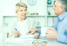 Middle-aged couple at table attentively study documents. And sign agreement royalty free stock image
