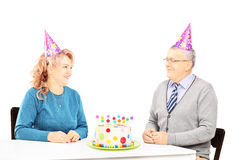 Middle aged couple on table with cake, looking at each other on Stock Photo