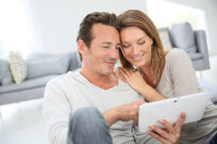 Middle-aged couple with tablet websurfing at home Stock Photo