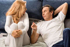 Middle aged couple talking, looking at each other and lying on bed at home. Upset middle aged couple talking, looking at each other and lying on bed at home royalty free stock photo