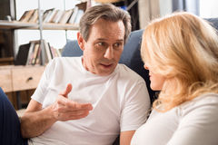 Middle aged couple talking and lying on bed at home Stock Photography