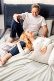Middle aged couple talking and lying on bed at home Stock Photos