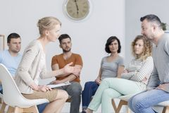Couple talking during assertiveness training. Middle-aged couple talking and solving problems during group assertiveness training royalty free stock image
