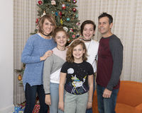 Middle-aged couple with their 3 daughters standing in front of a Christmas tree. Lovely middle-aged couple with their 3 beautiful young daughters smiling and Stock Photos