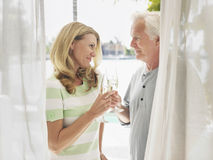 Middle Aged Couple Toasting Champagne Flutes. Side view of a middle aged couple toasting champagne flutes behind curtain Royalty Free Stock Image