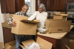 Middle-aged couple unpacking boxes. stock photo