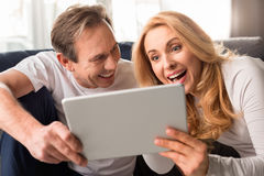 Middle aged couple using digital tablet at home Stock Photography