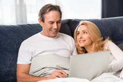 Middle aged couple using laptop and lying on bed at home Stock Photos