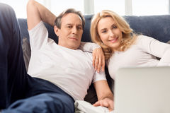 Middle aged couple using laptop and lying on bed at home Royalty Free Stock Photos