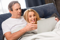 Middle aged couple using laptop and lying on bed at home Royalty Free Stock Photography