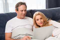 Middle aged couple using laptop and lying on bed at home Royalty Free Stock Photo