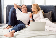 Middle aged couple using laptop and lying on bed at home Stock Photography