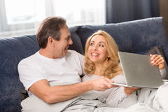 Middle aged couple using laptop and lying on bed at home Royalty Free Stock Images