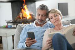 Middle-aged couple using smartphones Stock Photos