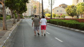 Middle-aged couple walking along the deserted street stock footage