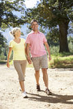 Middle Aged Couple Walking Through Countryside Stock Image